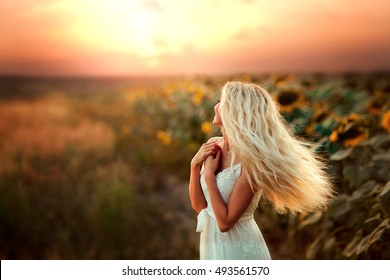 Beautiful blonde young model in white dress turns around back in sun light . Glow sun. Free happy woman.Art work. Warm photo. Amazing view and nature.Sunflowers background.