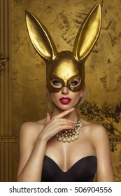 Beautiful blonde young woman in carnival gold rabbit mask with long ears