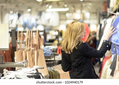 Beautiful blonde young woman choosing some clothes on discount in a boutique, holding a heart shaped balloon for valentine's day