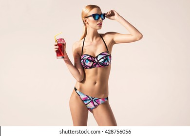 Beautiful blonde young woman in fashionable swimsuit. Bright colors, summer fashion photo