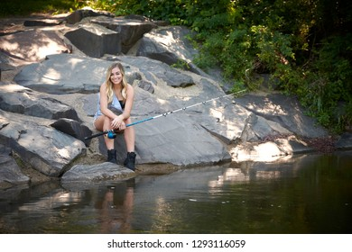 Beautiful blonde young woman fishing near creek wearing coveralls - seated on rock