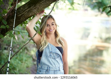 Beautiful blonde young woman fishing near creek wearing coveralls - standing next to tree
