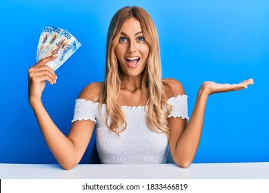 Beautiful blonde young woman holding 100 swiss franc banknotes celebrating achievement with happy smile and winner expression with raised hand