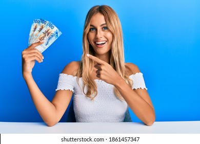 Beautiful blonde young woman holding 100 swiss franc banknotes smiling happy pointing with hand and finger