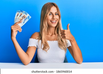 Beautiful blonde young woman holding 100 swiss franc banknotes smiling happy and positive, thumb up doing excellent and approval sign