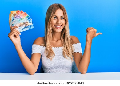 Beautiful blonde young woman holding swiss franc banknotes pointing thumb up to the side smiling happy with open mouth