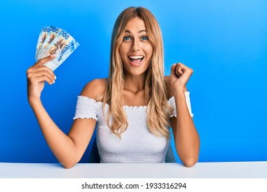 Beautiful blonde young woman holding 100 swiss franc banknotes screaming proud, celebrating victory and success very excited with raised arm
