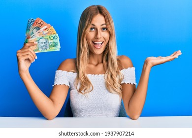 Beautiful blonde young woman holding australian dollars celebrating achievement with happy smile and winner expression with raised hand