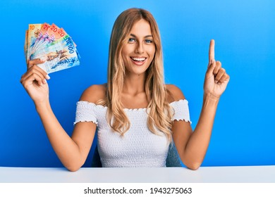 Beautiful blonde young woman holding swiss franc banknotes smiling with an idea or question pointing finger with happy face, number one