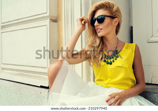 Beautiful blonde young woman holding sunglasses wearing fashionable clothes sitting on stairs
