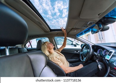 Beautiful blonde young woman looks in open hatch on a roof of the modern car after a rain. Raindrops on a glass roof of the car