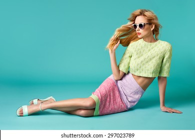 Beautiful blonde young woman in nice clothes, round white sunglasses, high heels sandals. Fashion Photo