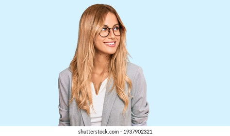Beautiful blonde young woman wearing business clothes looking away to side with smile on face, natural expression. laughing confident.
