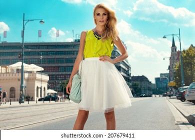 Beautiful blonde young woman wearing dress and walking on the street