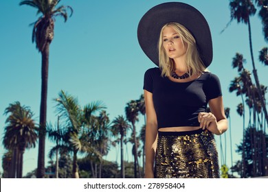Beautiful blonde young woman wearing fashionable clothes, big black summer hat walking on the street with palm trees. Fashion photo
