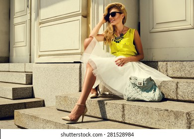 Beautiful blonde young woman wearing fashionable clothes sitting on stairs