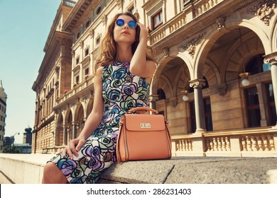 Beautiful blonde young woman wearing fashionable clothes, handbag, sunglasses sitting down in the city. Fashion photo
