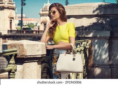 Beautiful blonde young woman wearing fashionable clothes, handbag, sunglasses posing in the city. Fashion photo