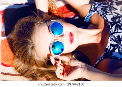 Beautiful blonde young woman wearing sunglasses,shorts,green top and handbag, laying on the beach,red lips,fresh face,model face,tan woman,sensual woman,long hair,reflection sunglasses,mirrored glass