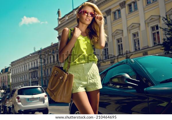 Beautiful blonde young woman wearing sunglasses, shorts, green top and handbag walking on the street