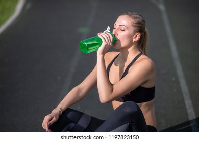 Beautiful blondel resting after workout at stadium, girl sat down to relax, drinking water from green bottle.
