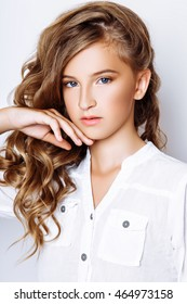 A beautiful blond-haired 13-years old girl in studio on white background