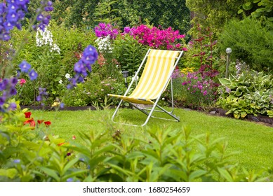 A beautiful blooming flower garden with yellow deck chair on a green lawn in summer