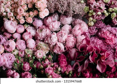 Beautiful blossoming freshly delivered flowers at the florist shop: cymbidium orchids, peony hermione ranunculus, roses, carnations, ozotamnus, eustoma in ombre pink and magenta colors