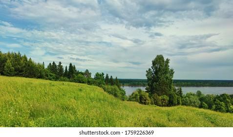 beautiful blue cloudy sky over a green hillside near the river