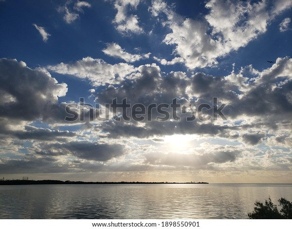 A beautiful blue cloudy and sunny sky. With the sun shining bright and like a spotlight.