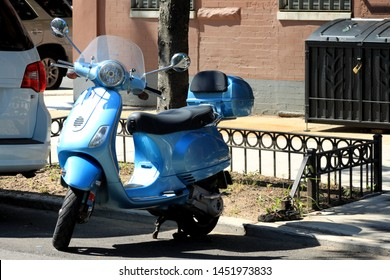 beautiful blue electric moped scooter bike parked in the weeksville section of crown heights on a sunny summer day in Brooklyn NY July 15 2019