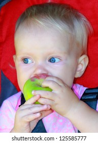 Beautiful blue eyed baby eating the apple Portrait