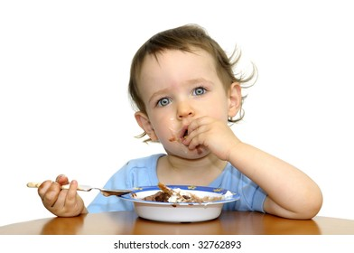 Beautiful blue eyed baby eating ice cream with a spoon isolated in white