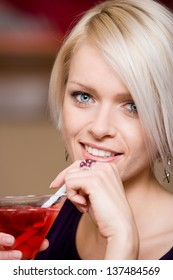 Beautiful blue eyed blond woman sipping a martini cocktail through a straw, closeup head portrait