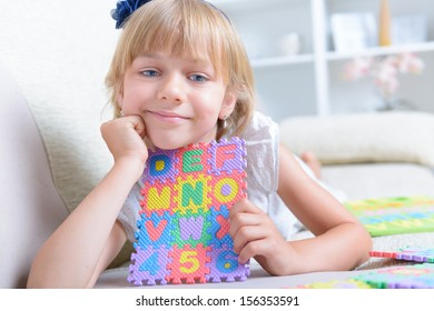 Beautiful blue eyed girl laying on the couch with alphabet letters puzzle