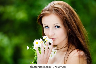 Beautiful Blue Eyed Woman Holding Flowers and smiling to a camera. Beauty Portrait. Green Background.