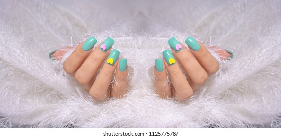 beautiful blue green gel polish on fashionista woman fingernails decorated with small cute colorful pink yellow heart isolated on white soft fur background