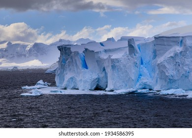 Beautiful blue ice cliffs and blue ice crevasses of a tabular blue iceberg from a melting tidewater glacier floating off the stunning Antarctic scenery of the Antarctic Peninsula of Polar Antarctica