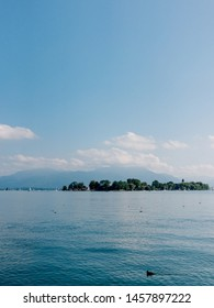 Beautiful blue lake Chiemsee against spectacular mountains and sky during sunny day