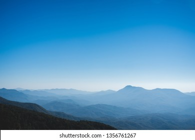 Beautiful blue landscape with white fog mountains.