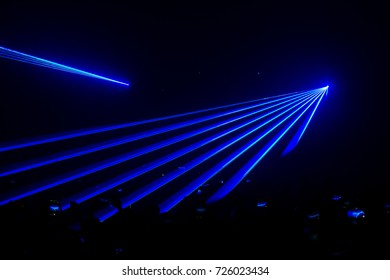 Beautiful blue laser beam in concert with crowded people holding the smartphone.