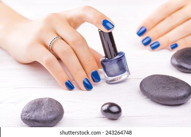 beautiful blue manicure with black stones on the white
