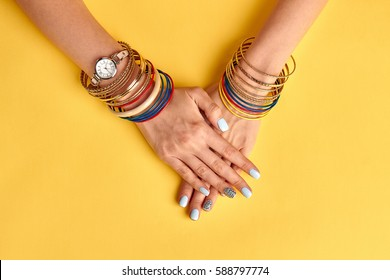 Beautiful blue manicure on yellow background. Many multi-colored bracelets on the women's hands. Beautiful jewelry and watches.