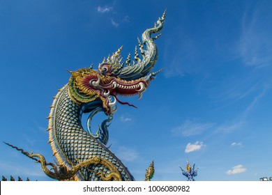 Beautiful blue naga sculpture with blue sky and white cloud on the sunny day at the public temple, Wat Rong Sua Ten, Chiang Rai, Thailand. Naga is a very great snake, found in the Buddhism temples.