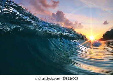 Beautiful blue ocean surfing wave under sunset