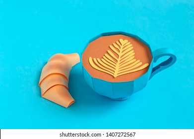 Beautiful blue paper cup with cappuccino and paper croissant. Volumetric handmade paper objects. Paper art and craft. Trendy hobby. Minimal artistic food concept