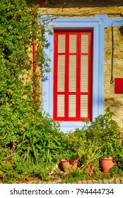 Beautiful blue and red window in mediterranean village house decorated with plant.
