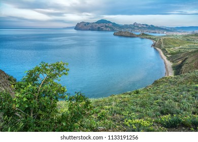 Beautiful blue sea, greenery on the shore and mountains in the background