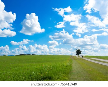 beautiful blue sky with cloud and meadow,bike lane on hill