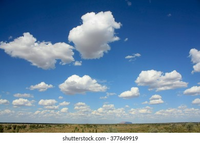A beautiful blue sky with clouds in Australia, near Uluru (Ayers Rock), in the background.